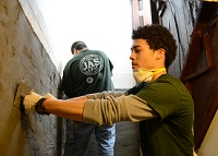 YouthBuild Student smoothing cement on wall
